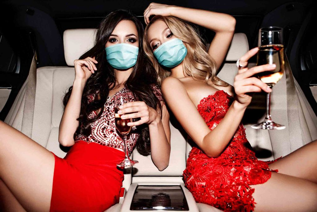 two sexy women celebrating with champagne in facemasks